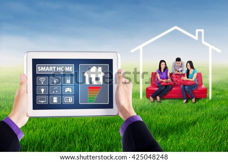 Image of two hands holding smart house system controller on the tablet with group of young people using smartphone on the sofa at field - stock photo