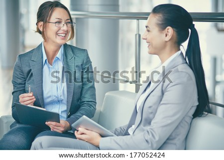 Image of two happy businesswomen sitting and talking - stock photo