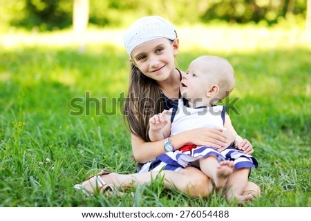 Image of two happy children having fun in the park, two sisters  on green grass in beauty summer day