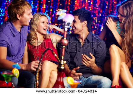 Image of two happy couples interacting in night club