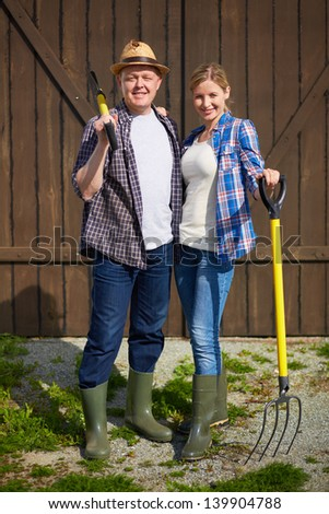 Image of two happy farmers with instruments - stock photo