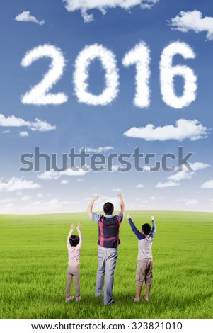 Image of two kids and his father standing on the meadow while raising hands and looking at numbers 2016