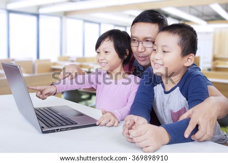 Image of two little students using laptop computer for studying with their teacher in the classroom - stock photo