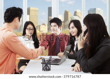 Image of two male entrepreneurs closing a business meeting by shaking hands in front of their partners at workplace