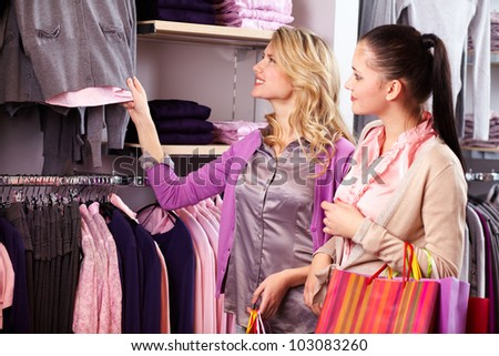 Image of two pretty girls looking at new collection of clothes in department store - stock photo