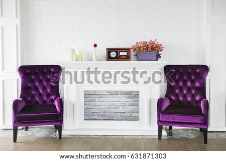 Image Of Two Purple Armchairs Near A Fireplace With Candles, Radio Player  And Flowers In