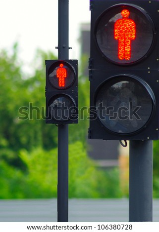 image of two red traffic lights on the background of trees - stock photo