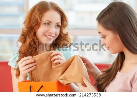 image of two teenage girls looking at clothes. Two smiling girls have coffee time - stock photo