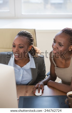 Image of two young african businesswomen using computer at meeting
