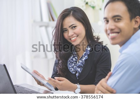 Image of two young asian business people at the meeting in the office