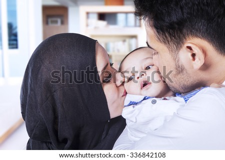 Image of two young asian parents kissing their baby's cheeks at home - stock photo