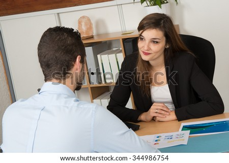 Image of two young business partners at meeting in a bright office