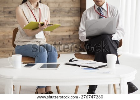 Image of two young business partners discussing plans or ideas at meeting - stock photo
