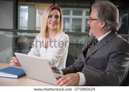 Image of two young business partners using laptop at meeting