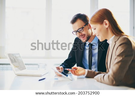 Image of two young business partners using touchpad at meeting - stock photo