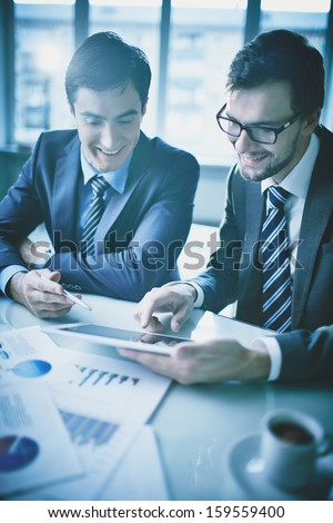 Image of two young businessmen discussing document in touchpad at meeting