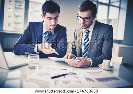 Image of two young businessmen discussing new project in office - stock photo