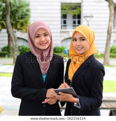 Image of two young businesswomen using touchpad outdoor meeting