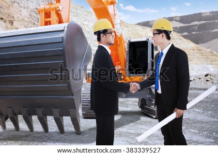 Image of two young engineer closing a deal by shaking hands near the excavator at the construction site