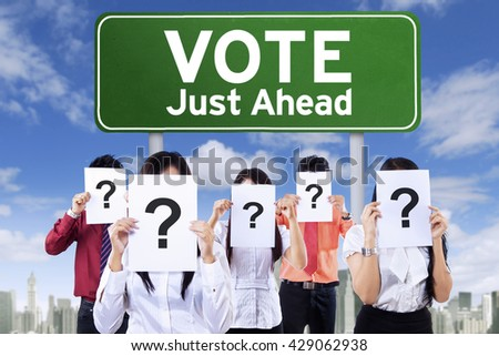 Image of unknown people covering face with question mark near the board with vote text - stock photo