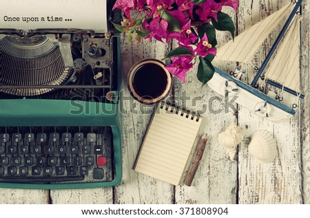 "image of vintage typewriter with phrase ""once upon a time"", blank notebook, cup of coffee and old sailboat on wooden table - stock photo"