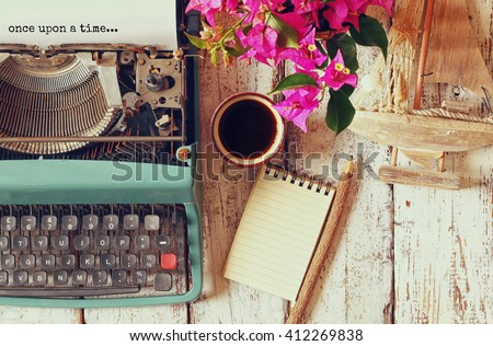 """image of vintage typewriter with phrase """"once upon a time"""", blank notebook, cup of coffee and old sailboat on wooden table  - stock photo"""