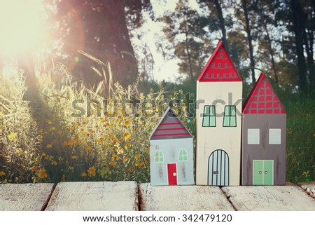 image of vintage wooden colorful houses decoration on wooden table in front of countryside forest.  - stock photo