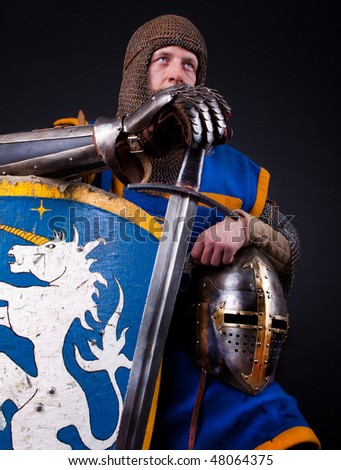 Image of warrior holding his helmet and shield with sword