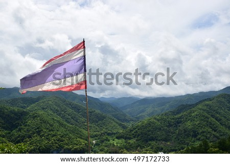 Image of waving Thai flag of Thailand with blue sky and Mountain background
