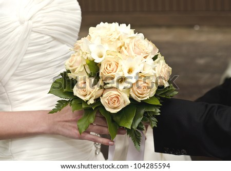 Image of wedding bouquet in hands of the bride and groom