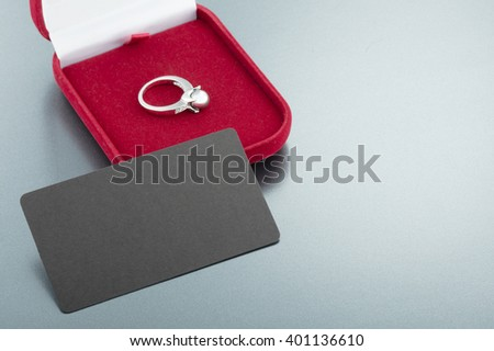 Image of wedding ring in a red gift box and invitation card  on gray background