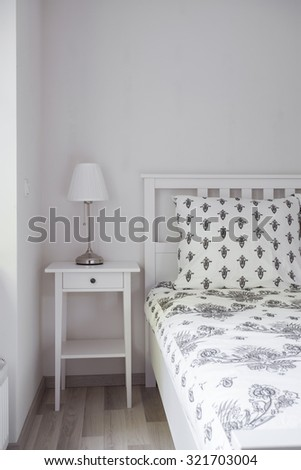 Image of white wooden nightstand with small lamp and bed - stock photo