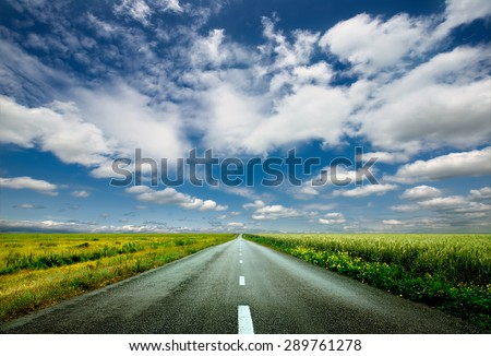 image of wide open prairie with a paved highway stretching out as far as the eye can see with beautiful small green hills under a bright blue sky in the summer time - stock photo