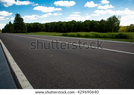 Image of wide open prairie with paved highway stretching out as far as eye can see with beautiful small green hills under bright blue sky in summer time. - stock photo