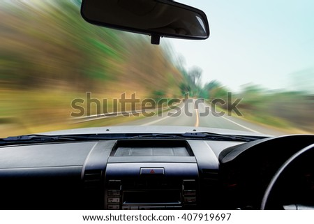 Image of windshield , blur image of motion as fast on the road.
