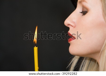 Image of witch looking at burning candle on black background