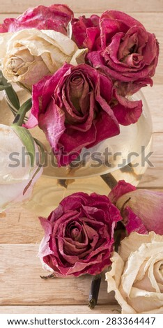 Image of withered red white roses on wood background.