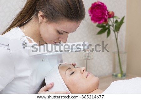 Image of Woman and cosmetician during facial spa procedure in the beauty treatment salon