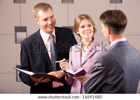 Image of woman and man looking at their partner while discussing business plan at meeting