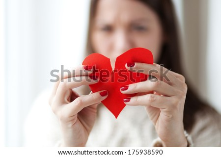 Image of woman tearing paper heart apart, shallow depth of field - stock photo