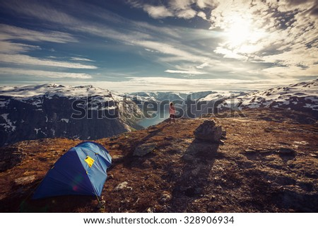 image of woman traveler standing on the mountain and looks into the distance on fjords,sunrise of mountains,camp - stock photo