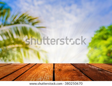 image of wood table and blur coconut tree for background usage. - stock photo