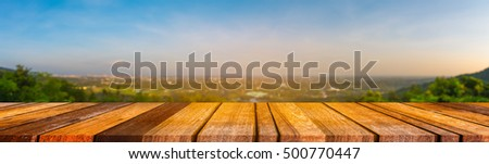 Image of Wood table with blur hills and city in background.