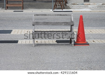 Image of wooden barricade with red road cone on the street at construction or repairment site - stock photo