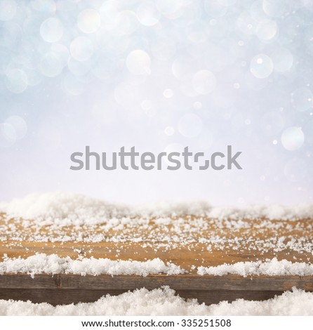 image of wooden old table and december fresh snow on top. in front of glitter background - stock photo