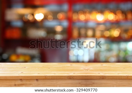 image of wooden table in front of abstract blurred background of restaurant lights  - stock photo