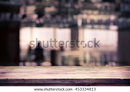 image of wooden table in front of abstract blurred background of restaurant lights, use for product display mock up.