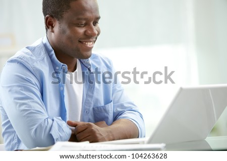 Image of young African businessman looking at laptop screen at workplace - stock photo