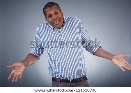 Image of young African man expressing uncertainty over grey background - stock photo