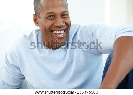 Image of young African man looking at camera and laughing - stock photo
